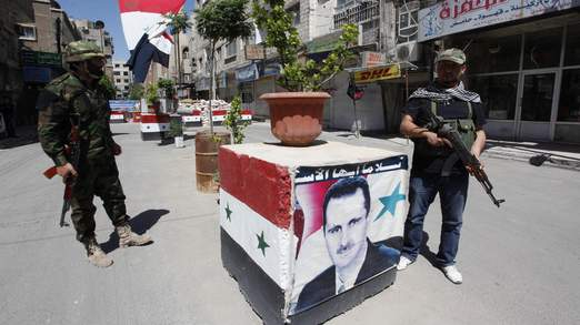 Security personnel loyal to Syria's President Assad stand guard at a checkpoint in Damascus